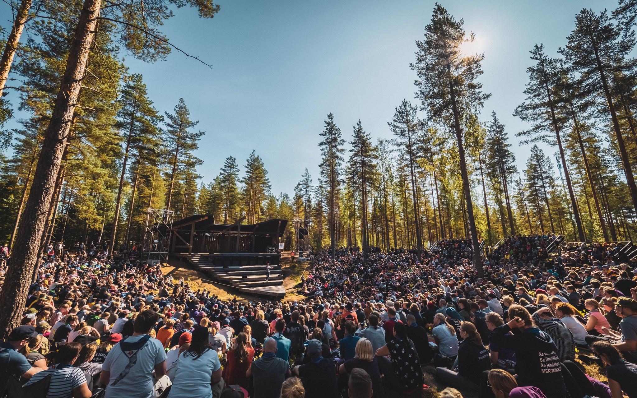Aurinkoinen metsämaisema, jossa on paljon ihmisiä kuuntelemassa puhujaa Johtajatulien lavalla.