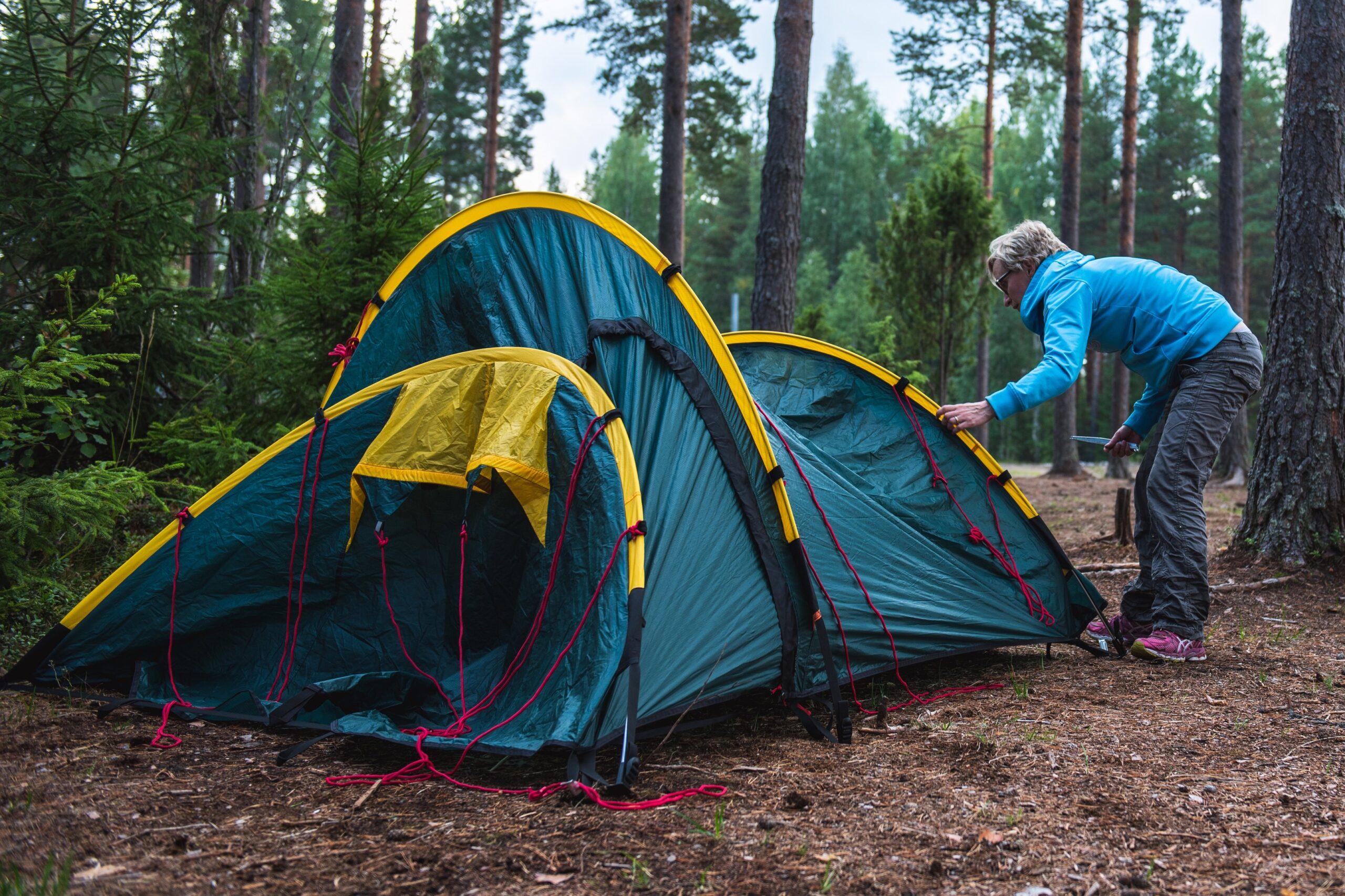 Partiolainen pystyttää telttaa