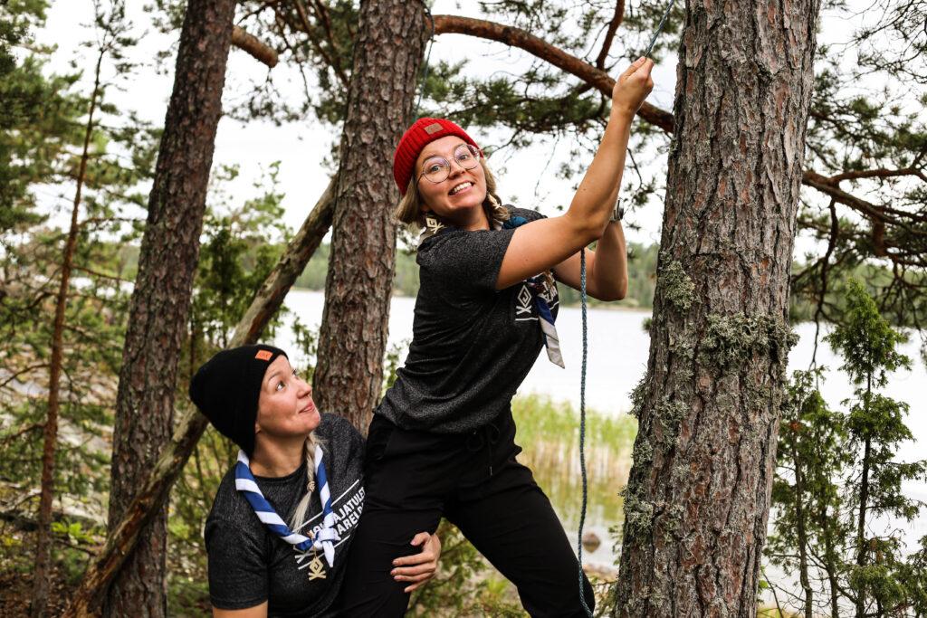 Tapahtumanjohtajat Milka ja Mimi kiipeämässä puuhun